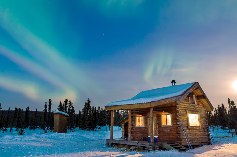 Cabin in Alaska with Northern Lights in the sky.