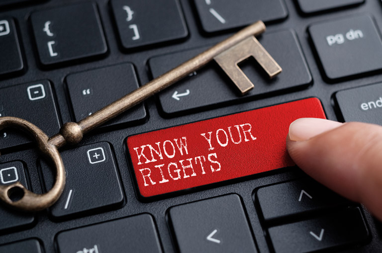 "Keyboard with antique key and finger pushing red button with ""KNOW YOUR RIGHTS"" on it."